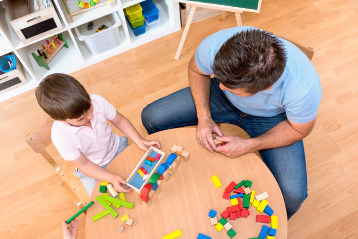 Father and son playing with toy blocks