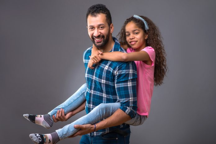 A young black man standing and caring his daughter on his back