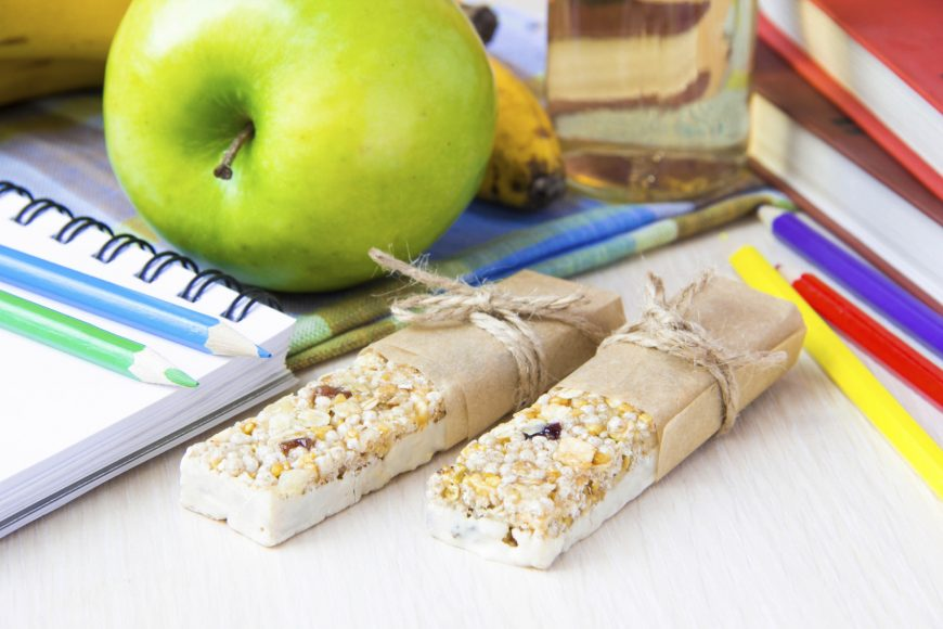 Healthy school lunch for child with stick berry muesli and green apple, books, notebooks and colorful pencils around