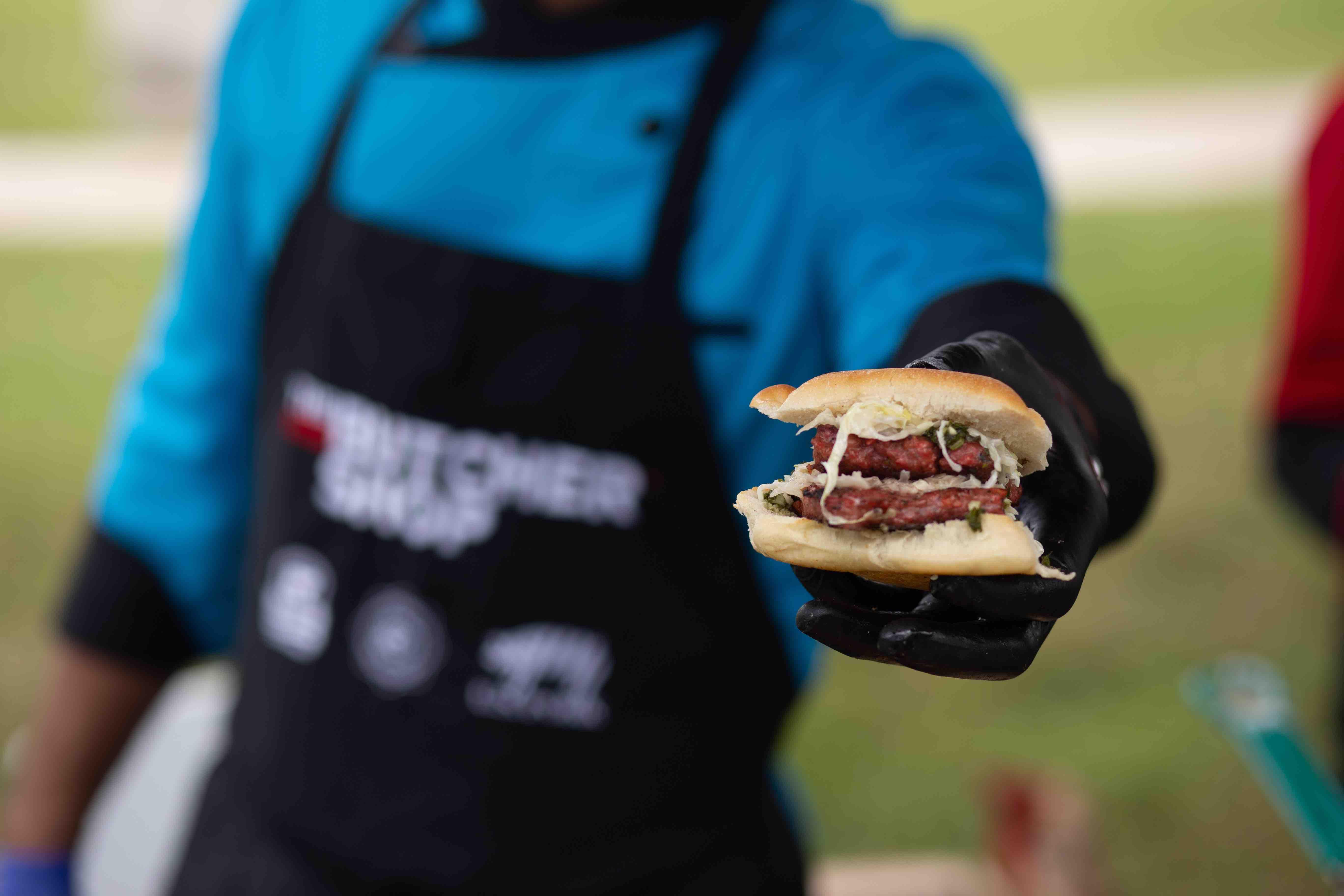 Chef ofrece una de las hamburguesas de Imex a los golfistas