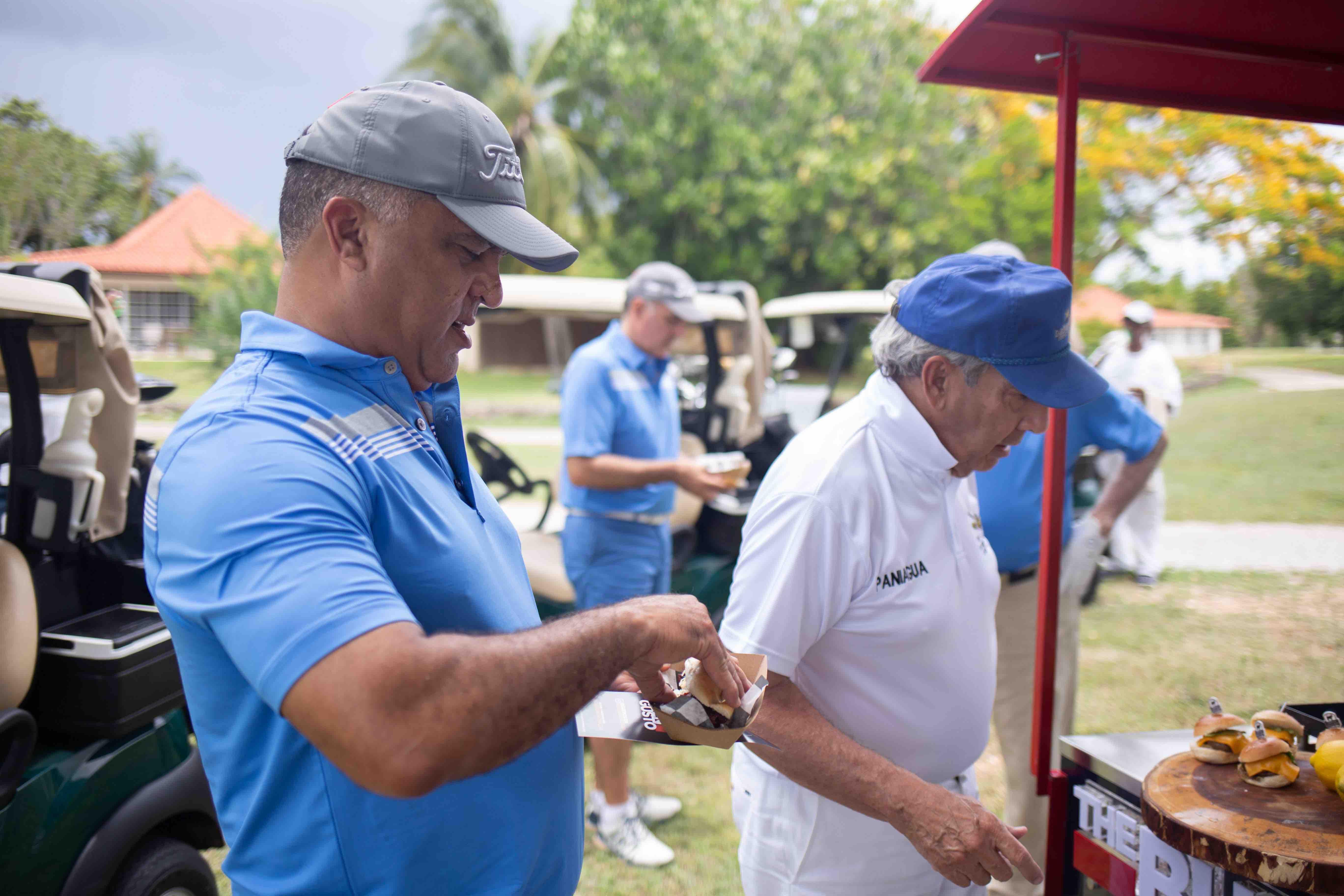 Golfistas disfrutando de los platos del stand de Imex