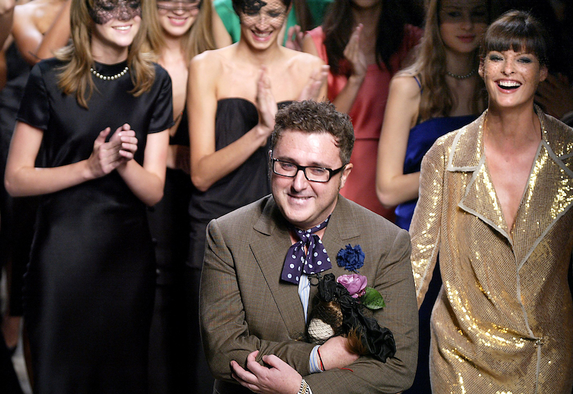 (FILES) In this file photo taken on October 12, 2003 designer Alber Elbaz acknowledges the audience alongside Canadian supermodel Linda Evangelista, (R) after his show for Lanvin 12 in Paris during the ready-to-wear Spring/Summer 2004 collections. Alber Elbaz, the fashion designer whose audacious billowing designs transformed the storied French house Lanvin into an industry darling before his shock ouster in 2015, has died aged 59, the Richemont luxury group said on April 25, 2021. (Photo by JEAN-PIERRE MULLER / AFP) (Photo by JEAN-PIERRE MULLER/AFP via Getty Images)