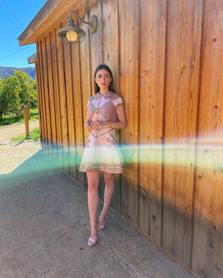 Lily Collins llevo la tendencia de vestido corto con una ornamentación de luz, firmado por Georges Hobeika.